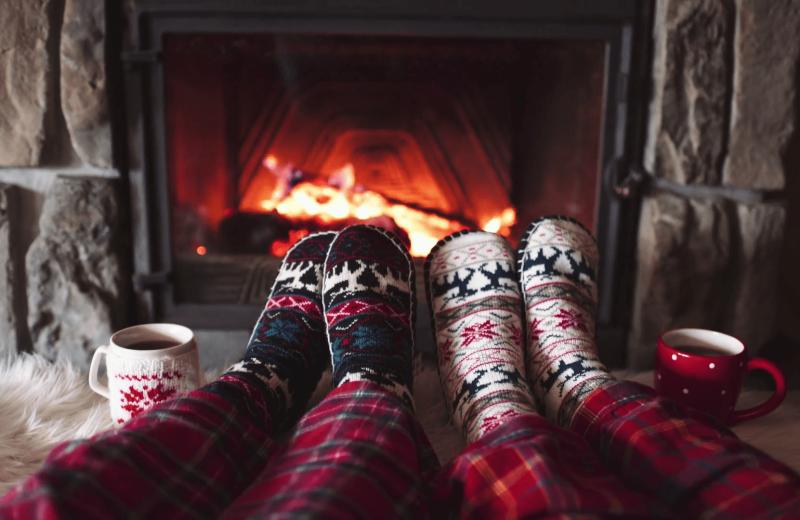 Couple by fireplace at Killington Rental Associates.