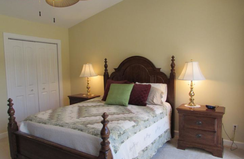 Master Suite with Queen Bed and view of pool and courtyard from balcony off bedroom
