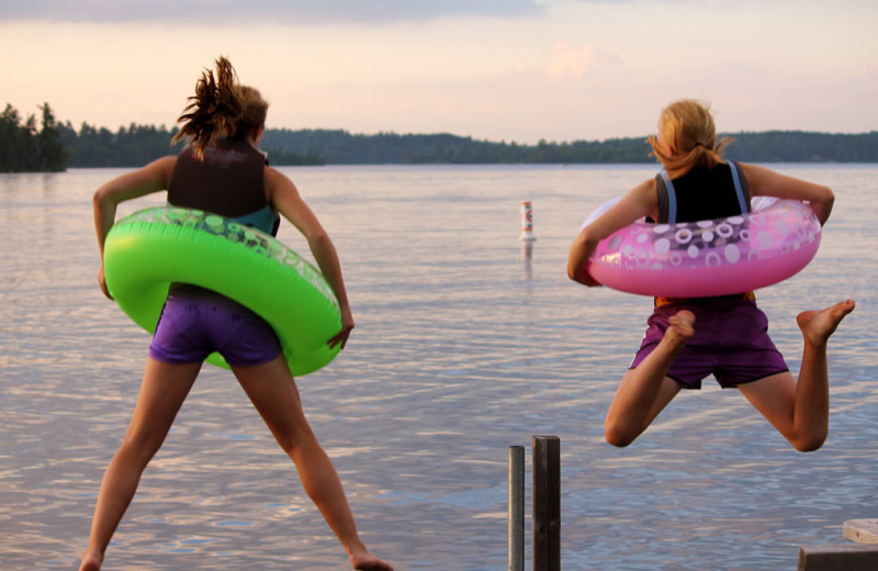 Two girls jumping off the dock into the lake.