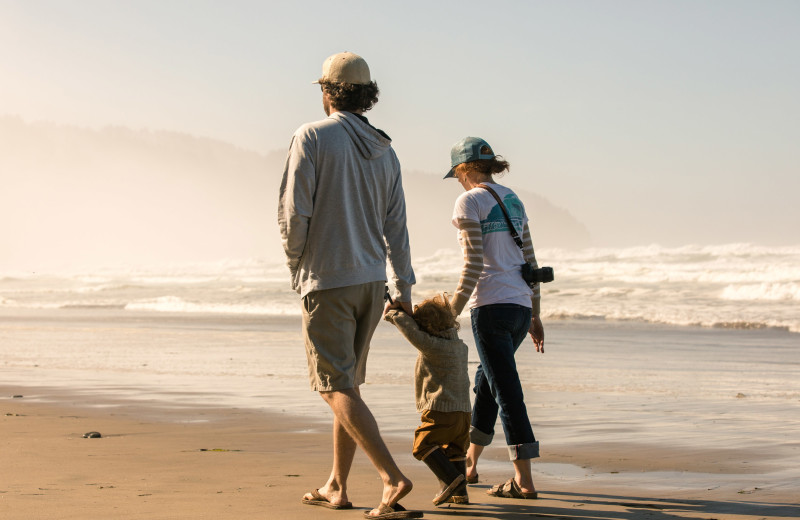 Family on beach at Beachhouse Vacation Rentals.