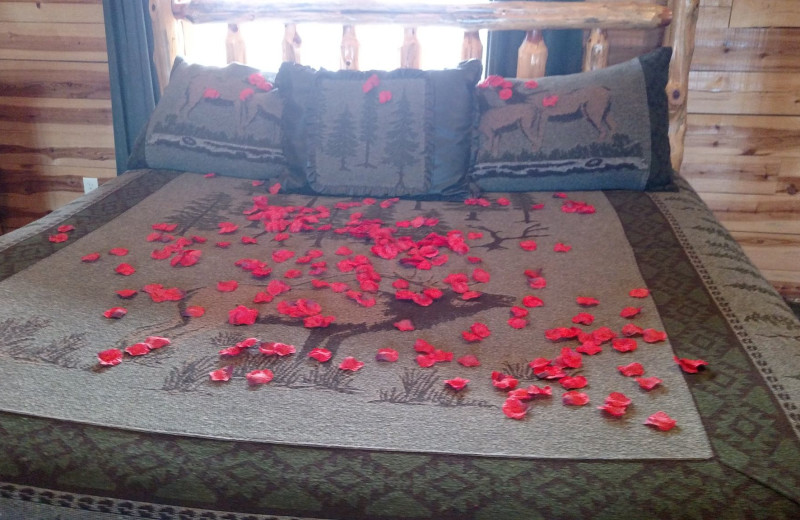 Bed with rose peddles at Lake Forest Luxury Log Cabins.