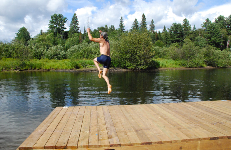 Jumping in lake at Wolf Den Hostel and Nature Retreat.