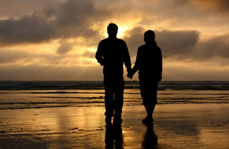Couple holding hands on beach at Old Town Inn.