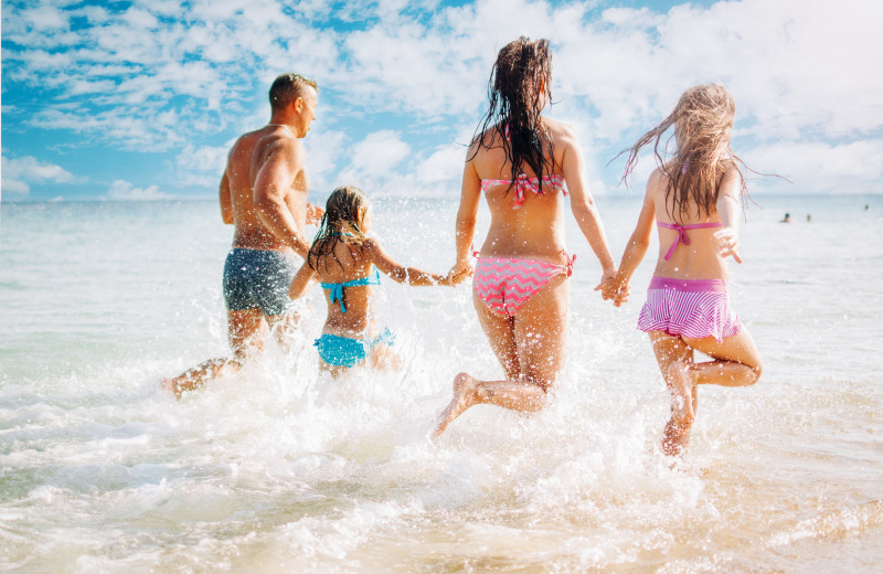 Family running into waves at Sea Star Realty.