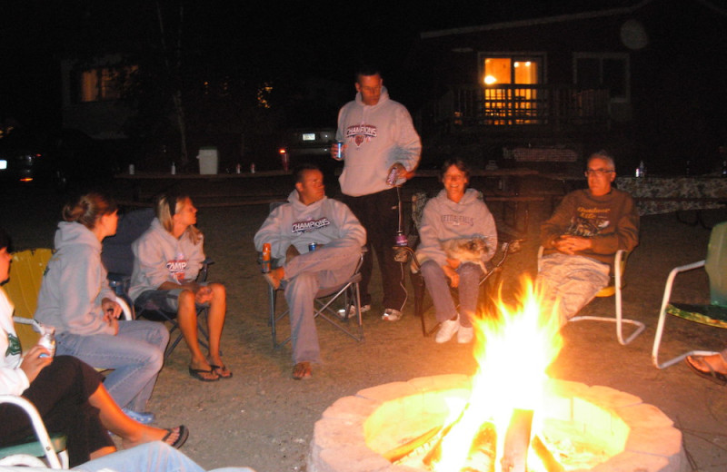 Family by the fire pit at Herseth's Tomahawk Resort.