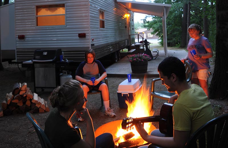 Family by the campfire at Lake George RV Park.