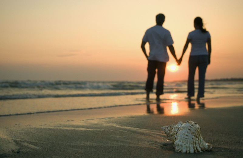 Couple holding hands on beach near Old Monterey Inn.