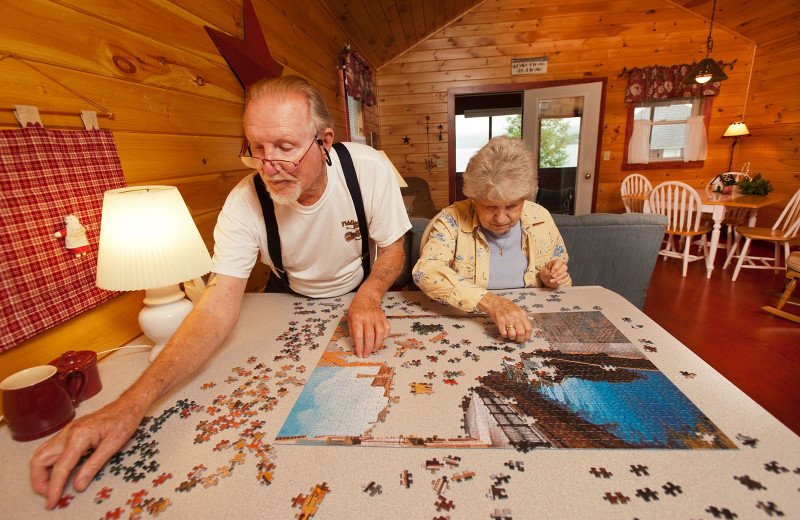Family making puzzle in lakeside cabin at Jackson's Lodge.