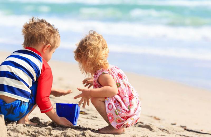 Kids on beach at No Worries Vacation Rentals.