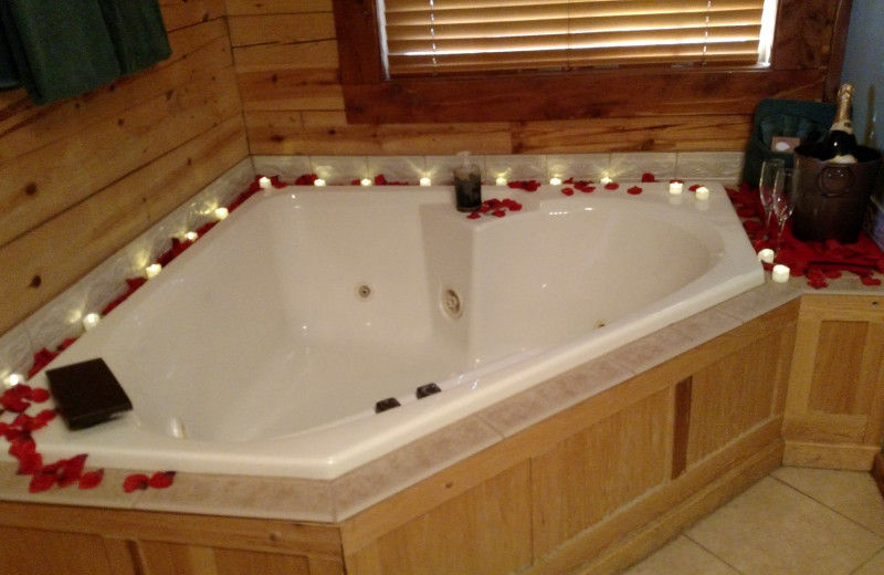 Hot tub with rose peddles at Lake Forest Luxury Log Cabins.