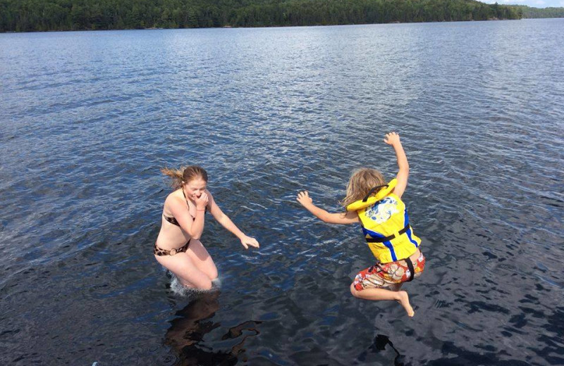 Kids jumping in lake at Dunlop Lake Lodge.