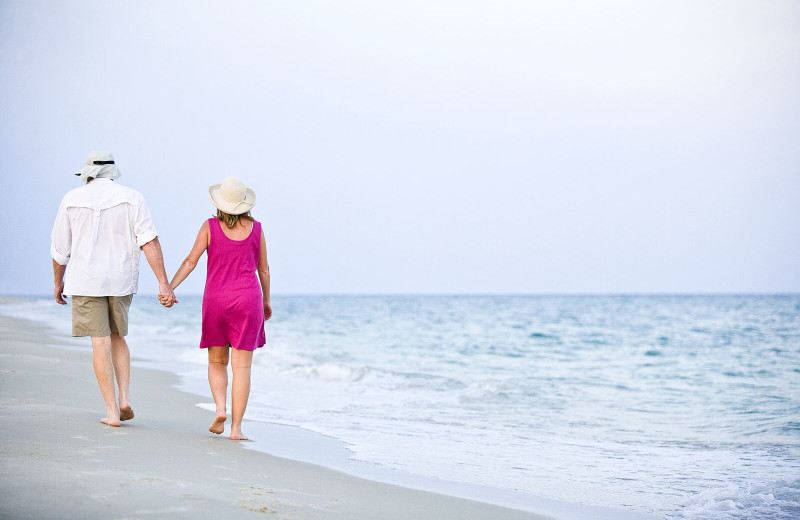 Couple holding hands walking on beach at Resort Vacation Properties of St. George Island.