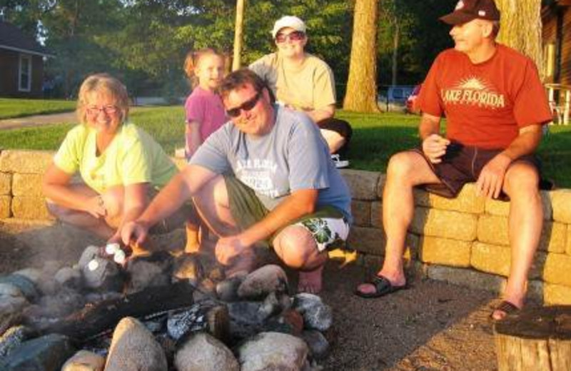 Family enjoying s'mores at the campfire on the beach