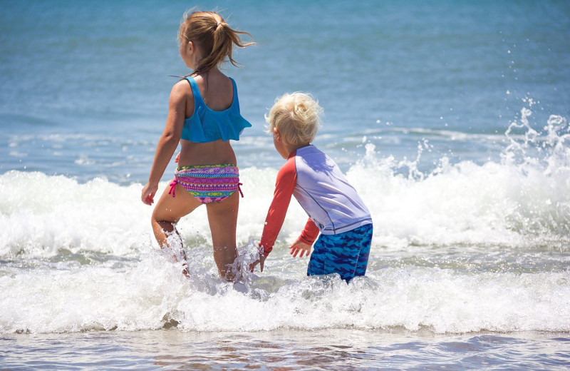 Kids playing on beach at Realty World - First Coast Realty.