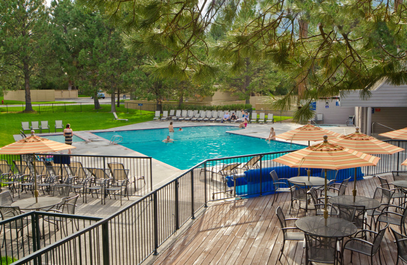 Outdoor pool with patio seating at Mount Bachelor Village Resort.