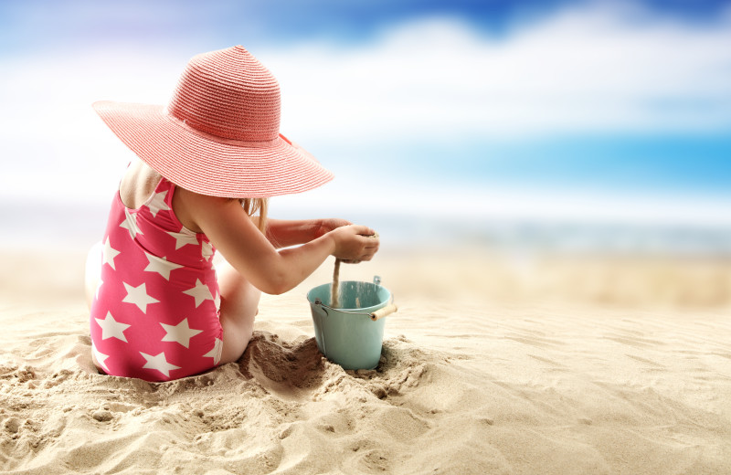 Baby with beach toys at Sea Star Realty.