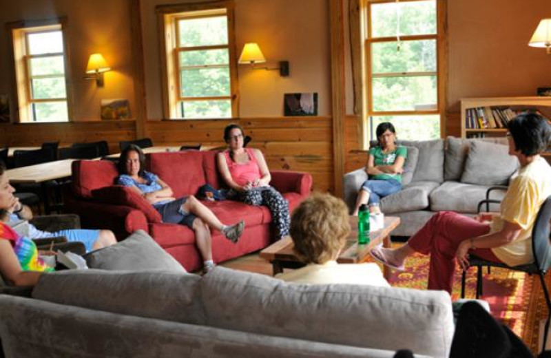 A group meets inside the Eco-Lodge Common Room at Common Ground Center.
