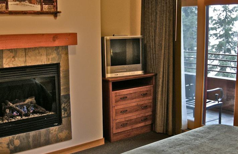 Guest bedroom with fireplace at The Lodge at Sandpoint.