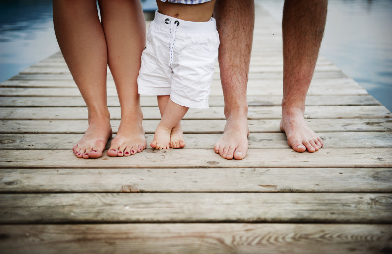 Family feet on dock at Sea Star Realty.