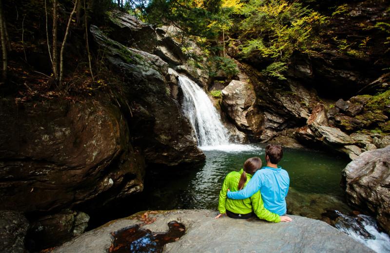 Couple and waterfall near Stowe Mountain Lodge.