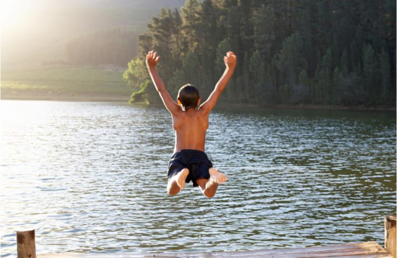 Jumping in the lake at The Woods At Bear Creek Glamping Resort.