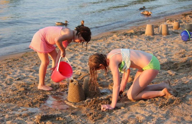Girls playing at the beach and building sand creations.
