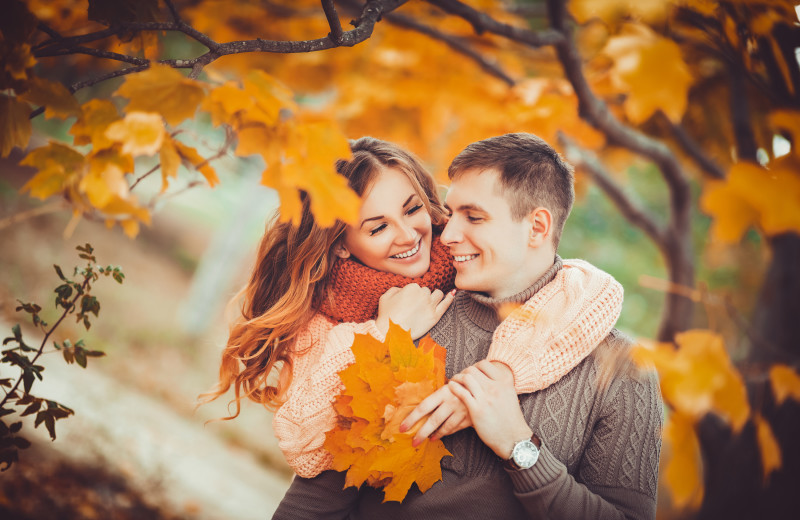 Couple hugging in fall leaves at Adobe Resort.