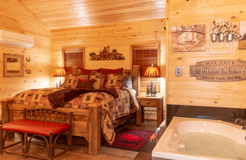 Cabin bed and hot tub at Harpole's Heartland Lodge.