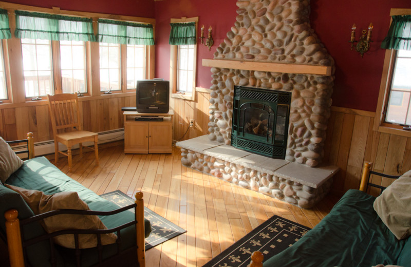 Cabin living room with fireplace at Tri Lake Timbers Resort.
