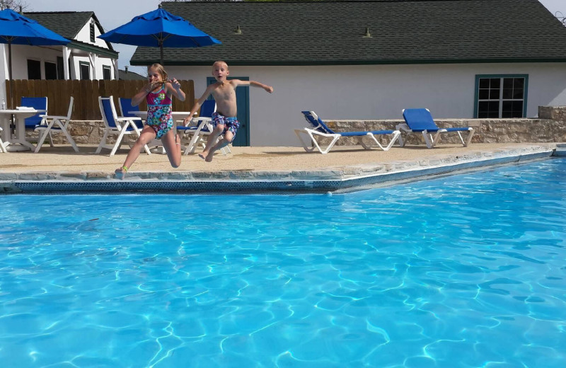 Kids jumping in pool at Peach Tree Inn & Suites.
