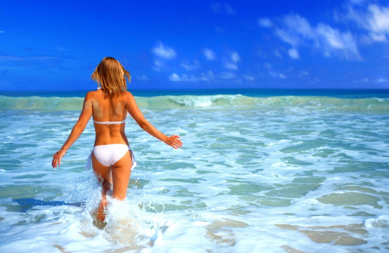 Walking into the waves at Gulf Winds Resort Condominiums.