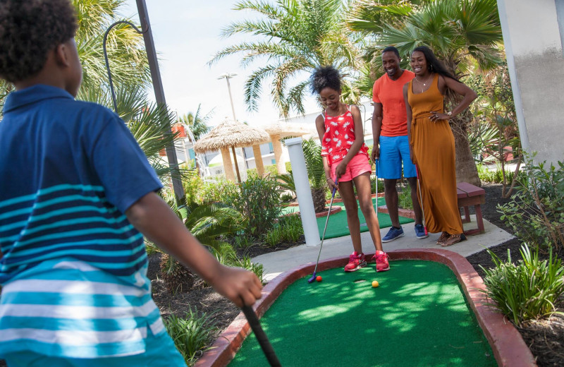 Family playing mini golf at Landmark Resort.