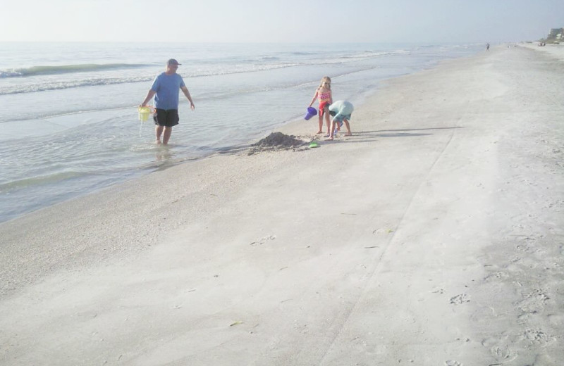 Family on the beach at Gulf Winds Resort Condominiums.