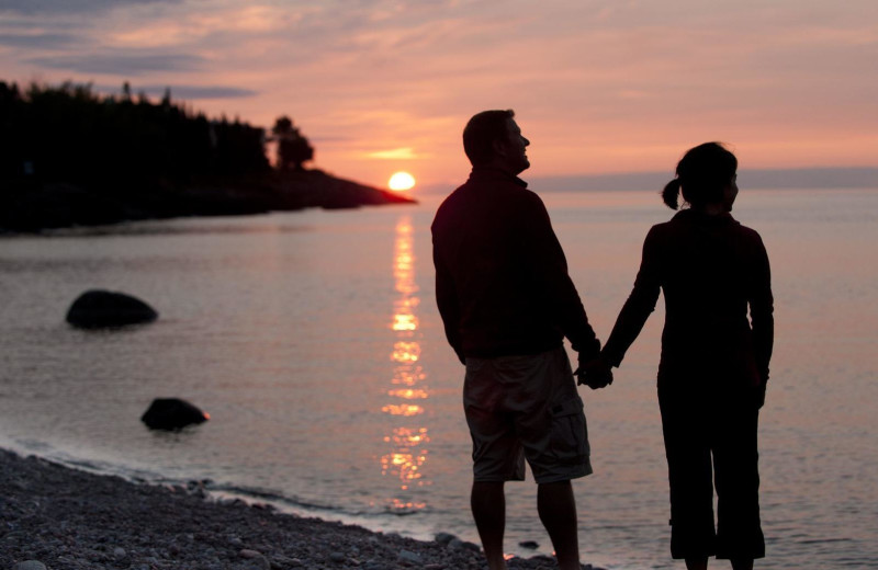 Couple holding hands on beach at Lutsen Resort on Lake Superior.