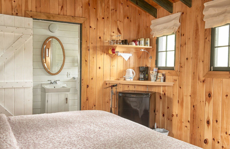Cottage bedroom with fireplace at The Lodge at Pine Cove.