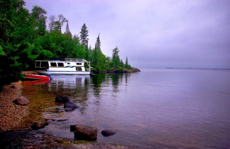 Houseboat docked on a sandy beach at Rainy Lake Houseboats.