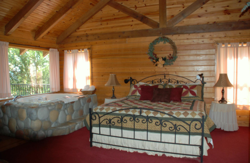 Cabin bedroom with hot tub at Whispering Hills Cabins.