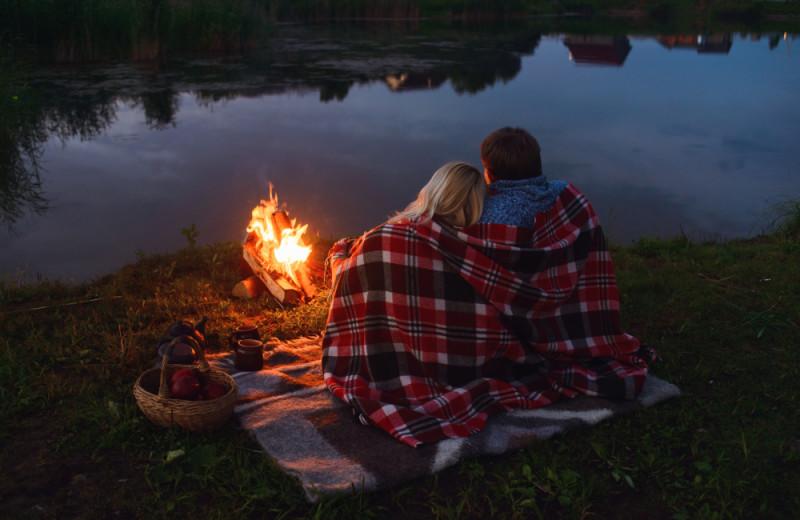 Couple cuddling around a camp fire near the lake.