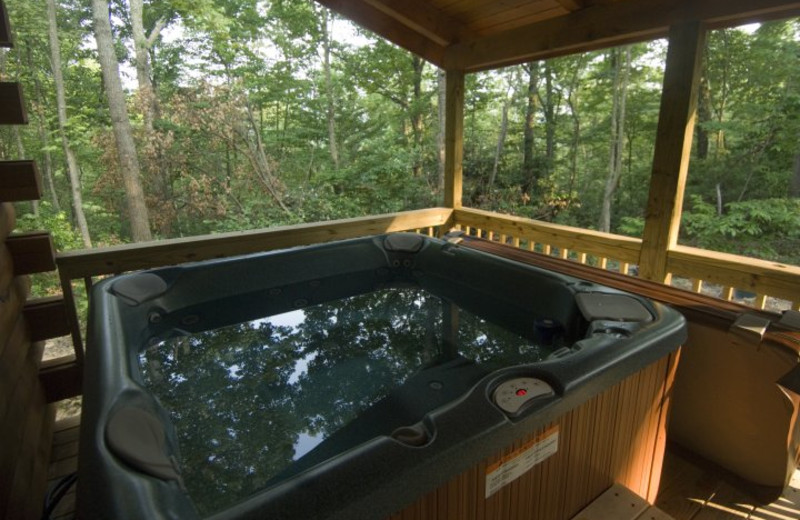 Cabin deck with jacuzzi at Country Road Cabins.
