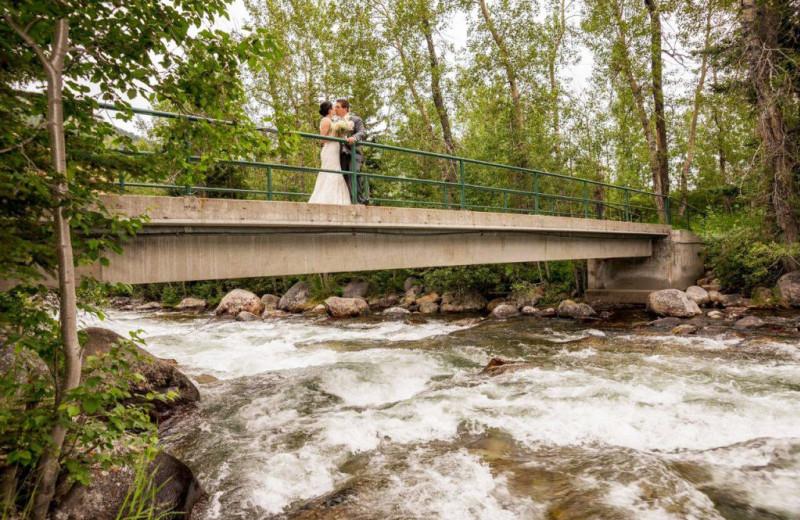 Wedding couple on bridge over creek at Rock Creek Resort.