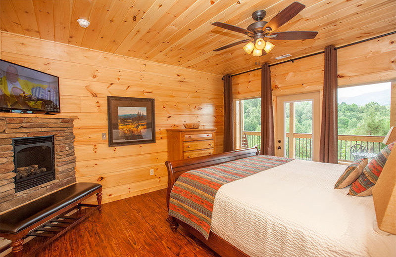 Cabin bedroom with fireplace at The Cabin Rental Store.