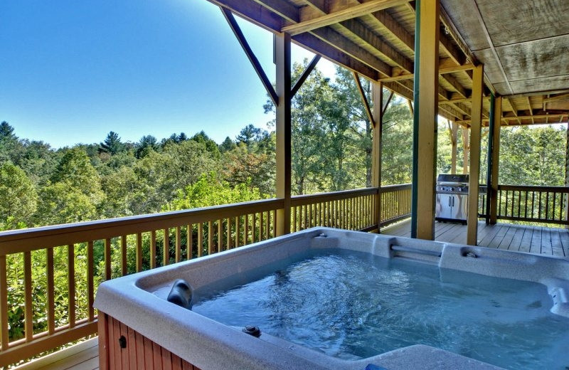 Deck view with jacuzzi at Southern Comfort Cabin Rentals.