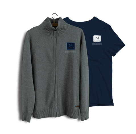 Mr. ShowerDoor's updated logo on a zippered grey sweater and a blue t-shirt.