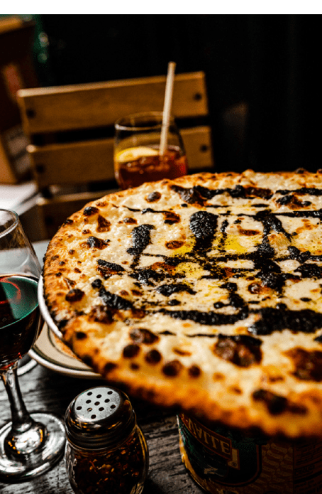 Close up of table with pizza and wine.