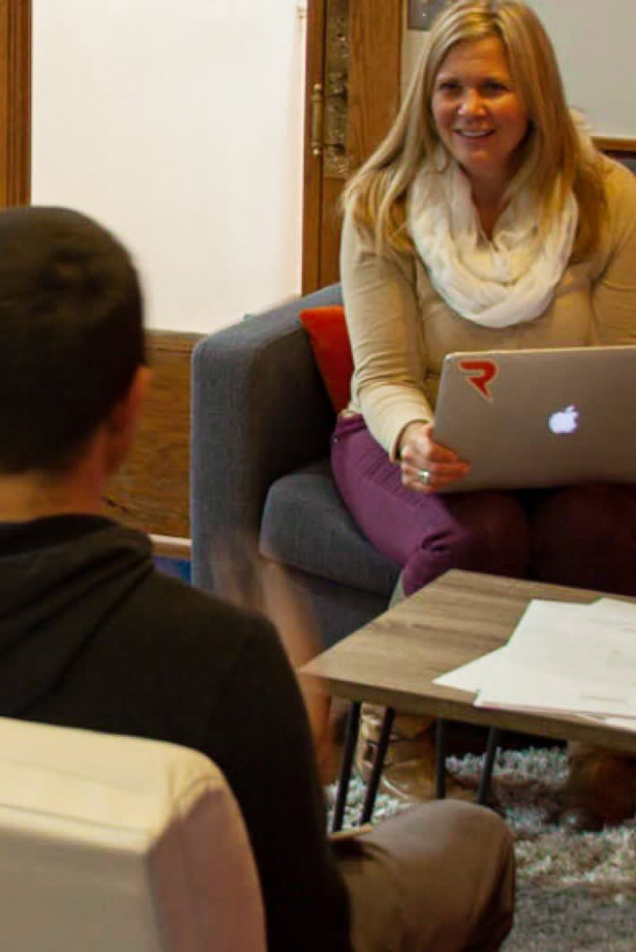Response CEO Carolyn Walker talking to a team member with an Apple laptop on her lap.