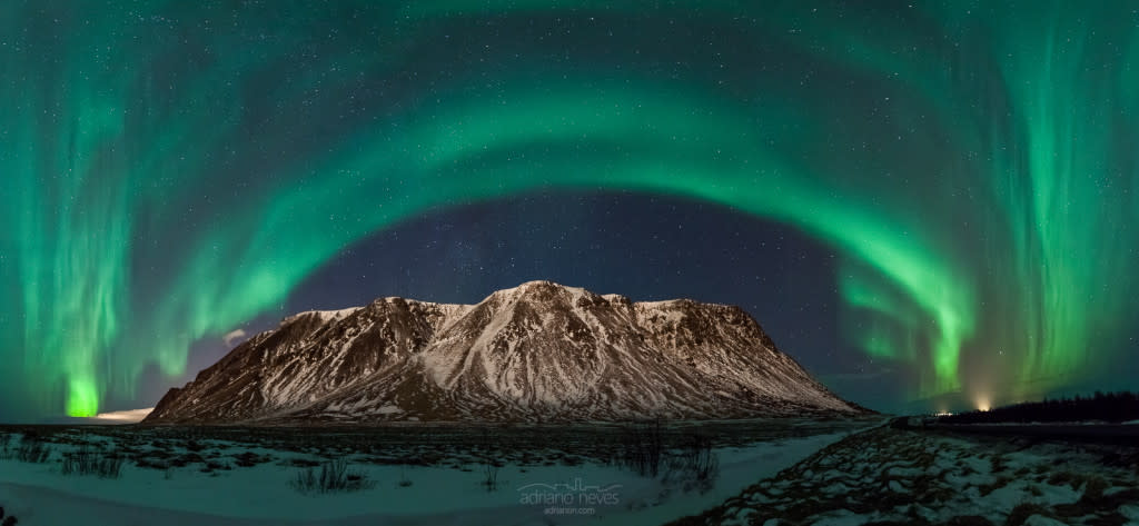 Northern lights or aurora borealis atmospheric phenomena over a snowy mountain in Iceland.