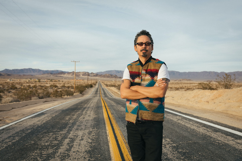 Guerrero standing arms crossed on an empty road