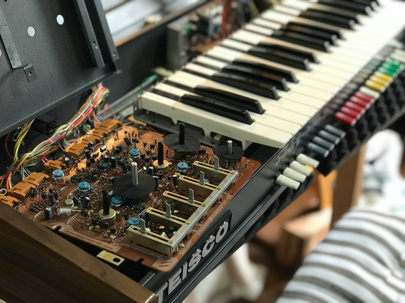 circuit board next to keyboard synth