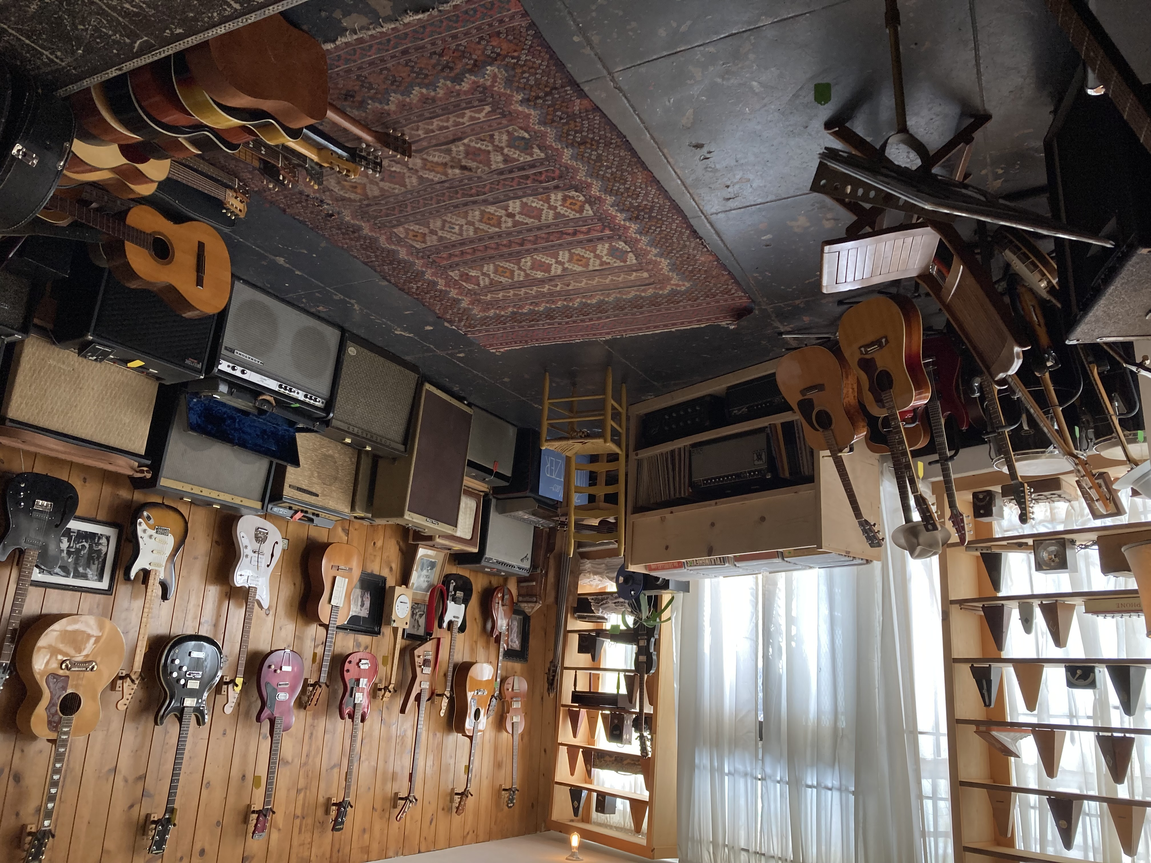 A wall of catalog guitars and vintage amps at Old Style Guitar Shop