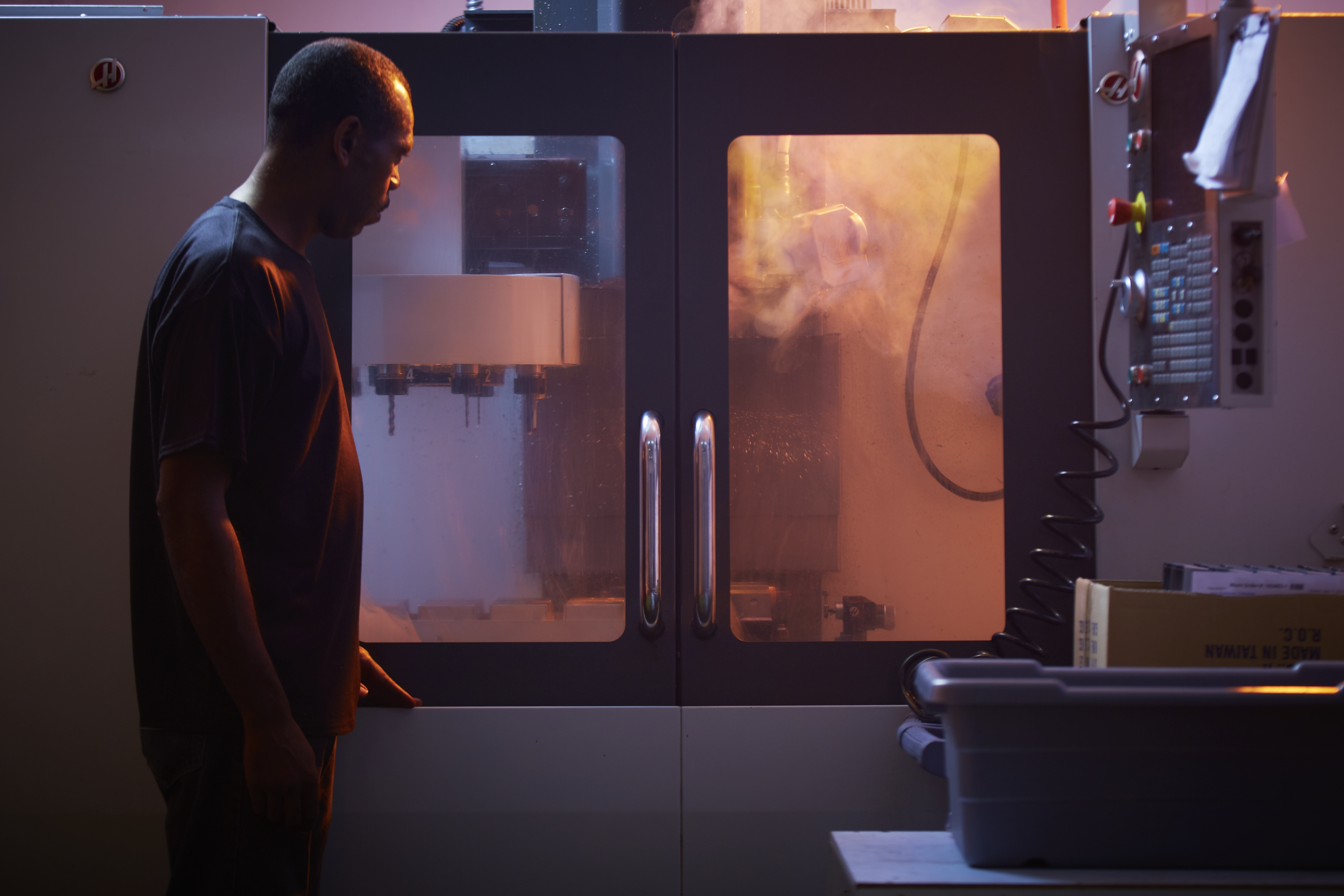 An employee inspects the enclosures as it passes through the CNC machine.